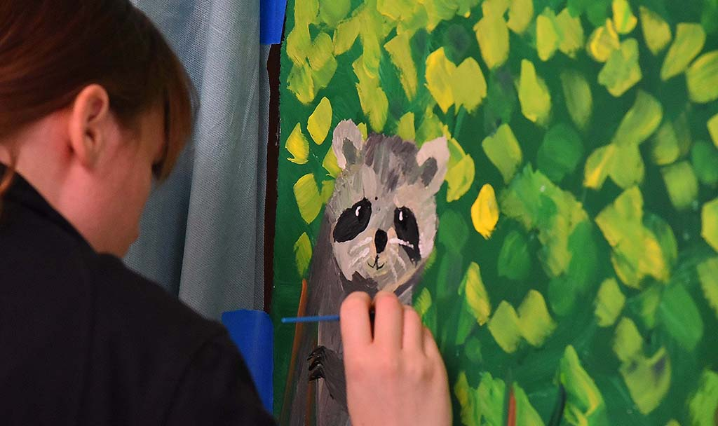 Megan Findahl, an intern for the for the San Diego River Park Foundation, works on a painting of raccoon for the mural at Parkway Plaza.