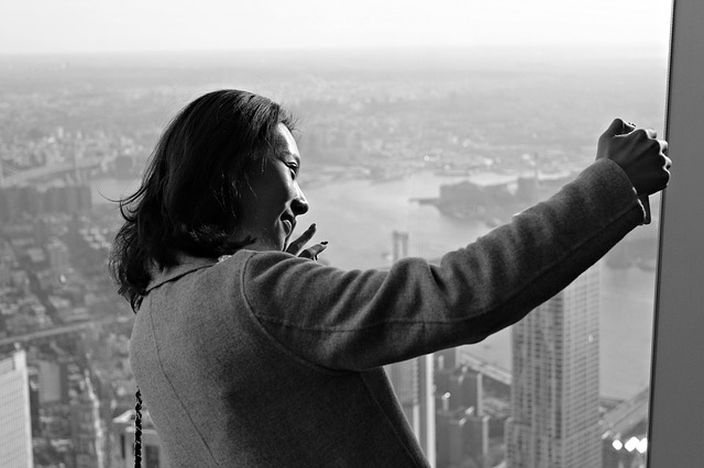 A woman taking a selfie atop a skyscraper