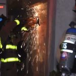 Firefighters use chainsaw to cut through door