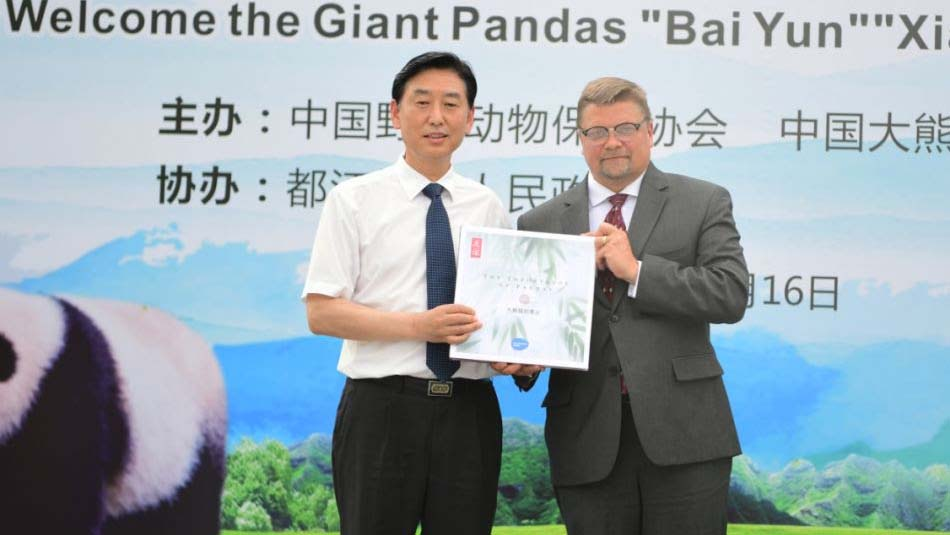 Shawn Dixon (right), chief operating officer of the San Diego Zoo,presented a book about the China-US giant panda cooperation to the China Giant Panda Conservation Research Center.