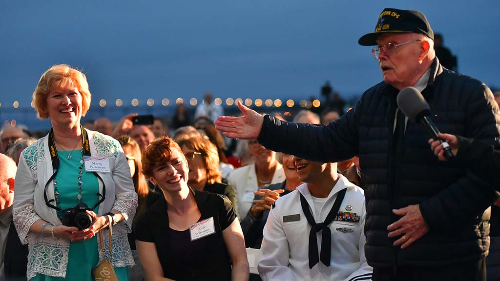 "Battle of Midway veteran Truxton ""T.K."" Ford gestures to his daughter, Merry Wiseman, while speaking of the importance of family."
