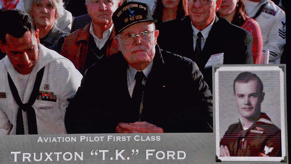 "Battle of Midway veteran Truxton ""T.K."" Ford is seen on the screen along with his Navy photo."