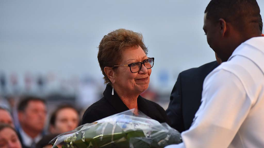 Tess Matz, spouse of deceased Battle of Midway veteran Lt. Cdmr. Rudy Matz receives flowers during the anniversary ceremony aboard the USS Midway.