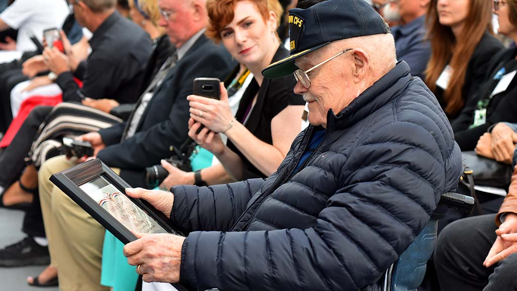 "Battle of Midway veteran Truxton ""T.K."" Ford, aviation pilot 1st class on the USS Yorktown, looks at an enlistment certificate he received."