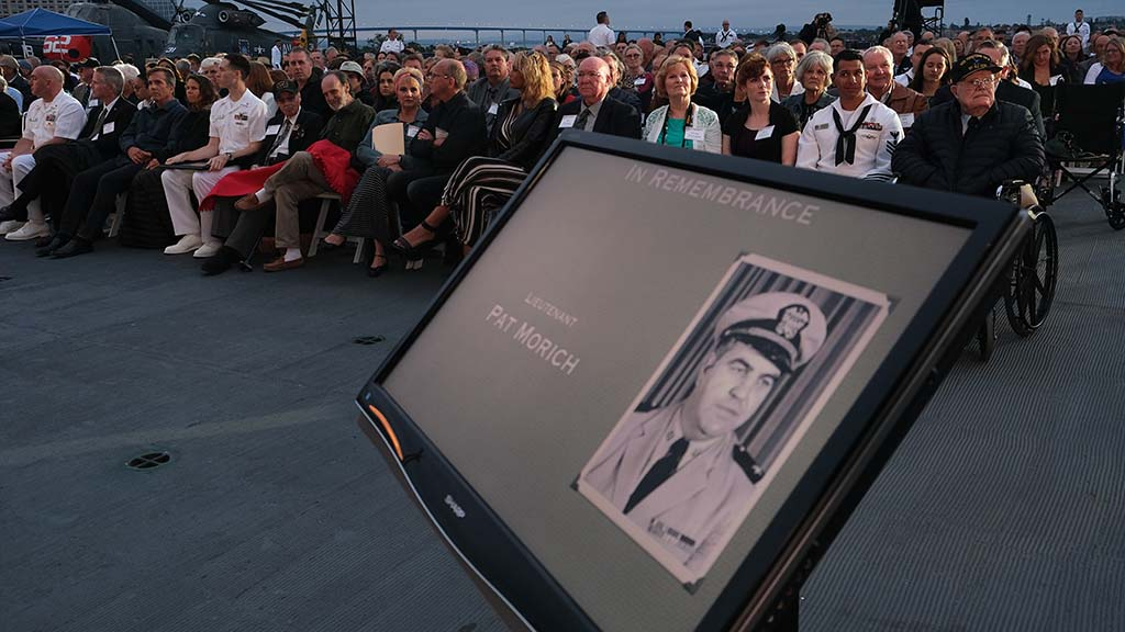 Attendees, including family members of Battle of the Midway veterans, watch tributes to their loved ones.