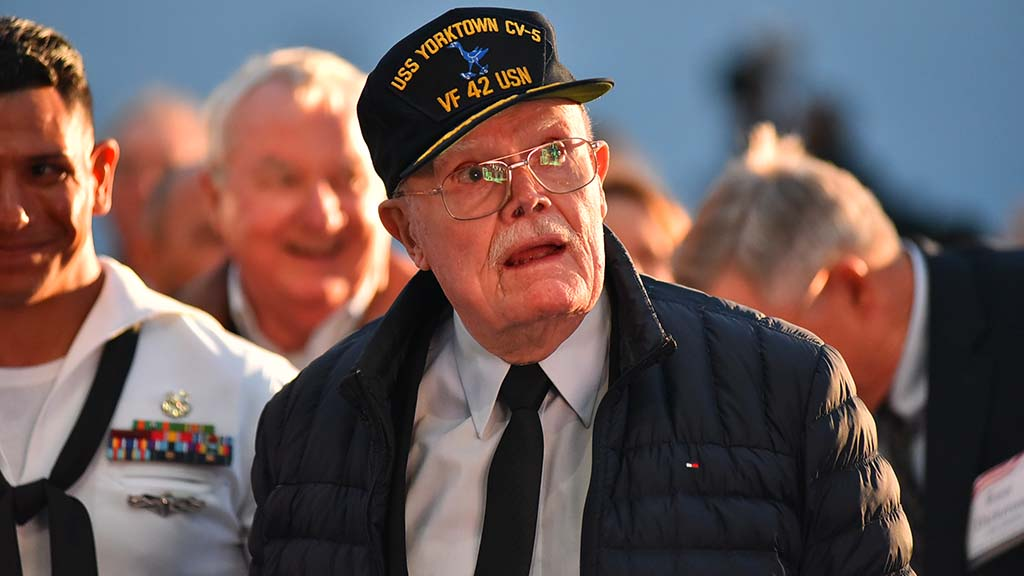 "Battle of Midway veteran Truxton ""T.K."" Ford watches a tribute to him on a screen aboard the USS Midway."