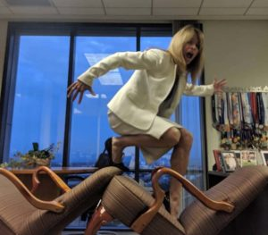 """University of San Diego School of Law alumnus Colleen Barney, with track medals behind her, used her Irvine law office as a """"Ninja"""" backdrop."""