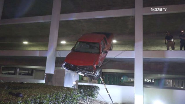 Truck hangs off 2nd floor if parking garage