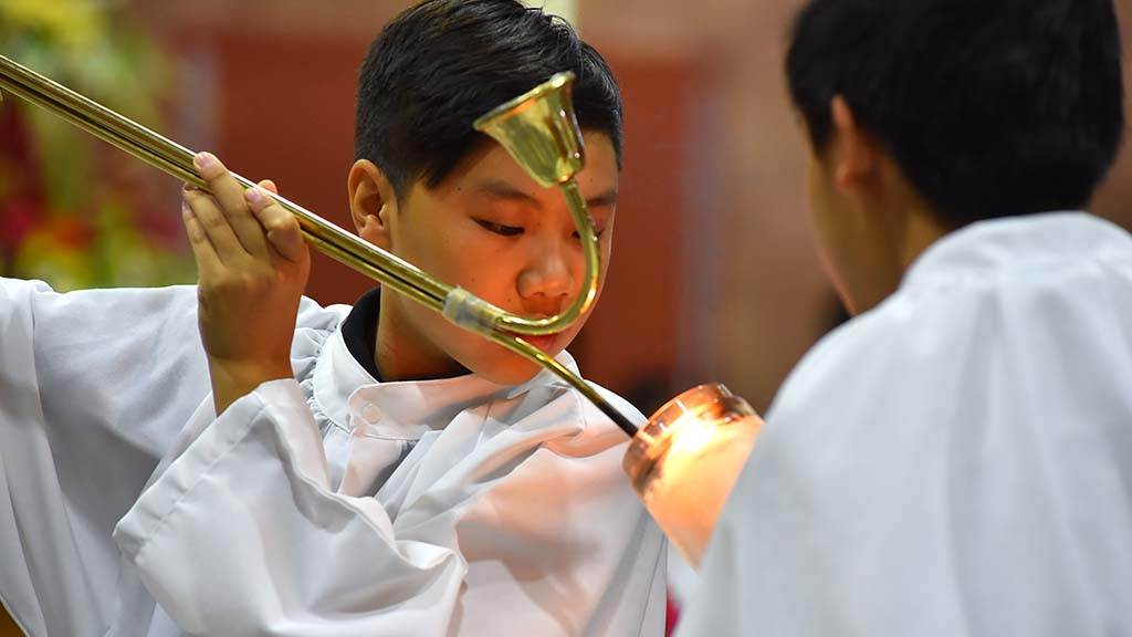 Altar servers light the candles before the multicultural Mass