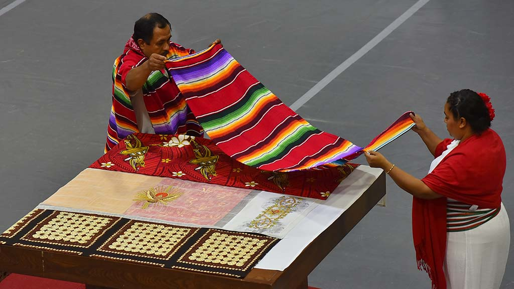 Members of the Mexican community place an cloth on the altar along with members of other communities represented in the Church.