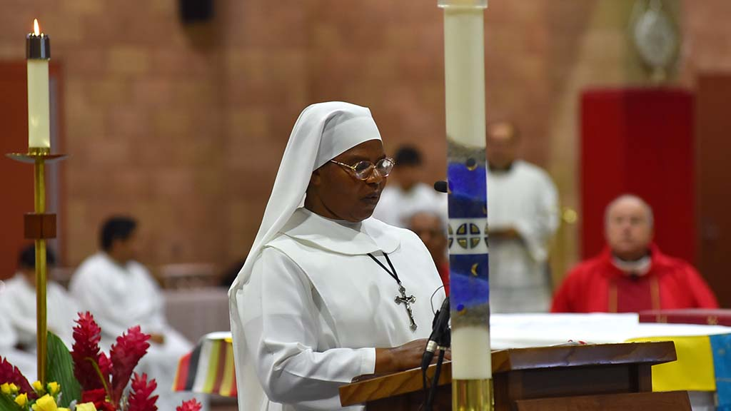 A sister from the African American community reads a Biblical passage during the multicultural Mass.