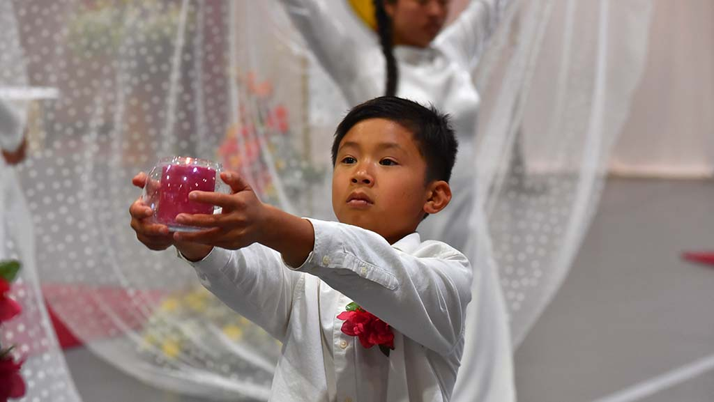 A young Vietnamese boy holds a lit candle during a performance during the offertory of the Mass.