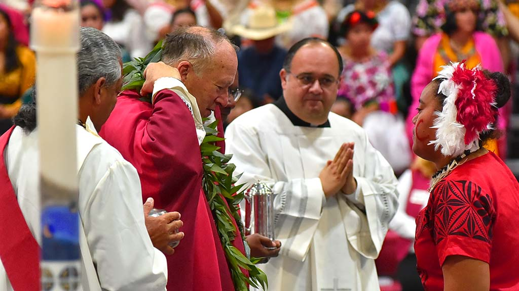 San Diego Bishop puts on a leaf lei during a multicultural Mass at Cathedral Catholic High School in Del Mar.
