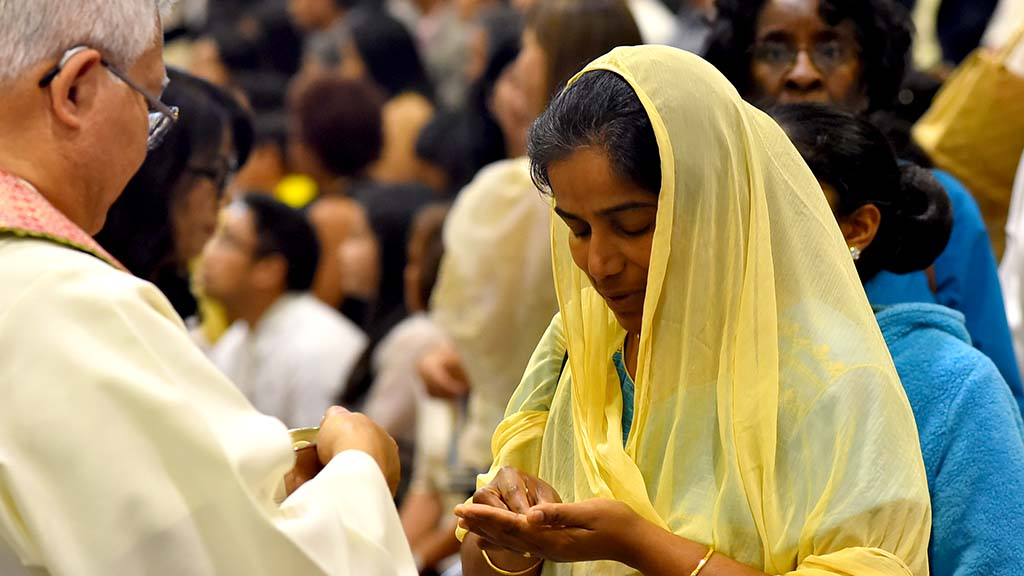 A woman from the Indian Catholic Community receives Holy Communion at the multicultural Mass in Del Mar.