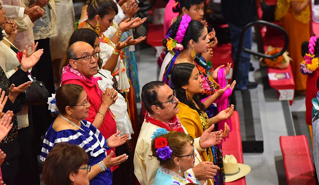 People from different cultures outstretch their hands during prayer at the multicultural Mass.