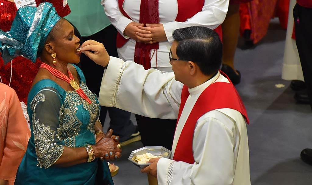 A woman from the African American Catholic community receives Holy Communion from a priest.