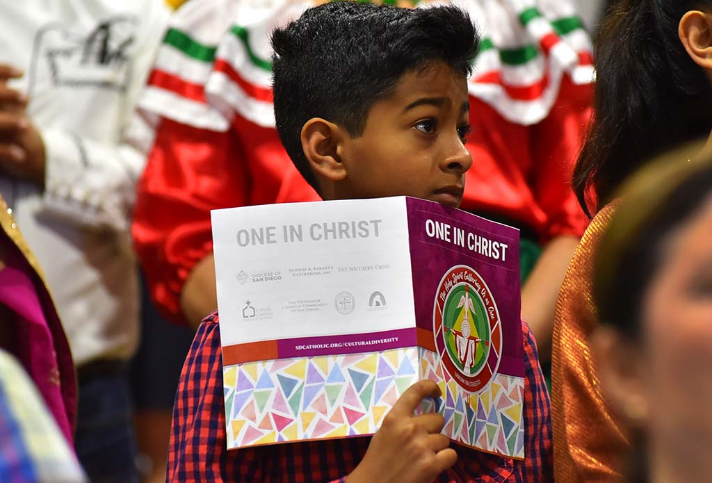 A young boy holds a program from the multicultural Mass in Del Mar.