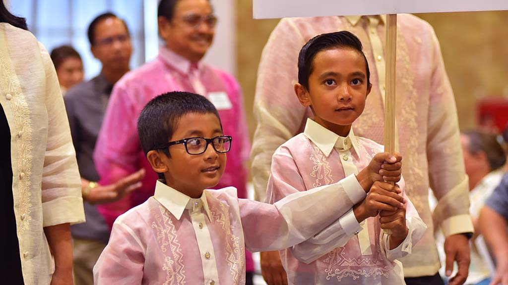 Young boys fro the Filipino community join the opening procession in the multicultural Mass.