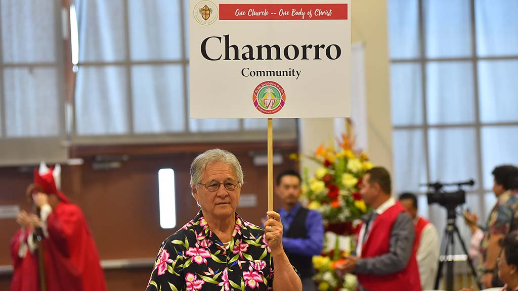 A member of the Chamorro community, indigenous people of the Mariana Islands, enters the gym at the beginning of the multicultural Mass at Cathedral Catholic High School.