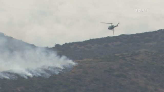 Firefighting helicopter over brush fire