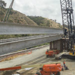 Construction workers place giant girders in Rose Canyone