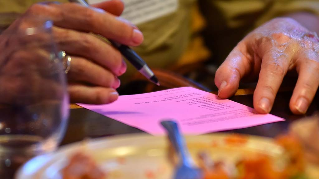 An attendee marks a straw ballot after the debate to indicate which candidate she thought won the first debate.