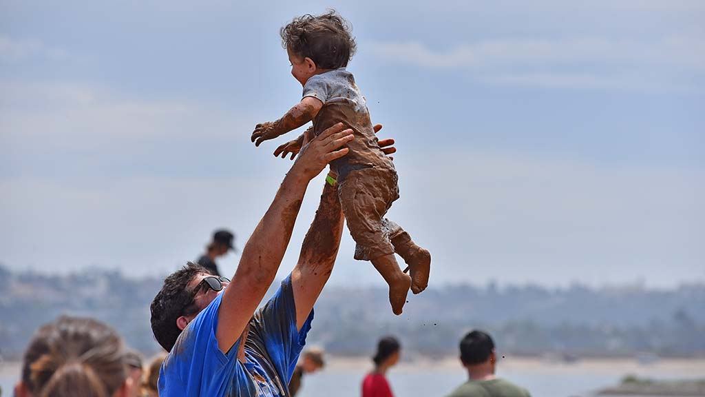 A man tosses a mud soaked child during Mud Day activities at Crown Point in Mission Bay.