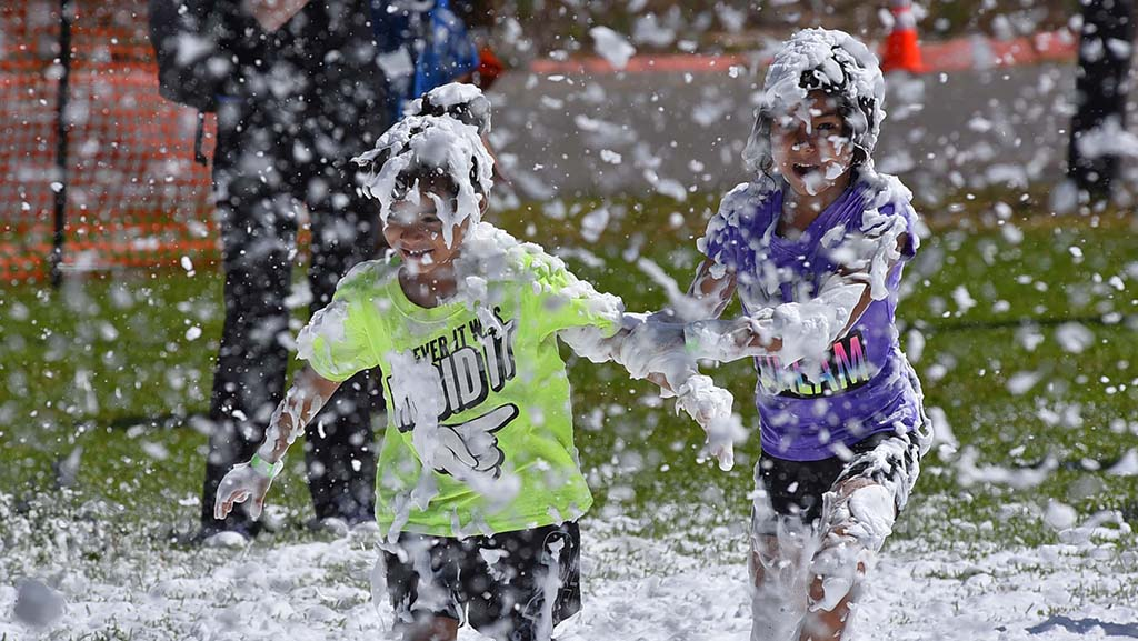 """Girls run through a """"Snofoam Snowstorm"""" made with Dr. Bronner's soap foam at the International Mud Day activities in Mission Bay."""