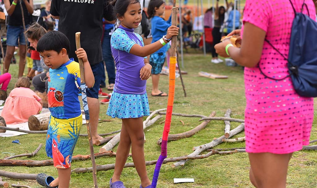Kyleigh Ordinario, 9, of Poway shows off a walking stick that she decorated with yarn at the Mud Day events in Mission Bay.