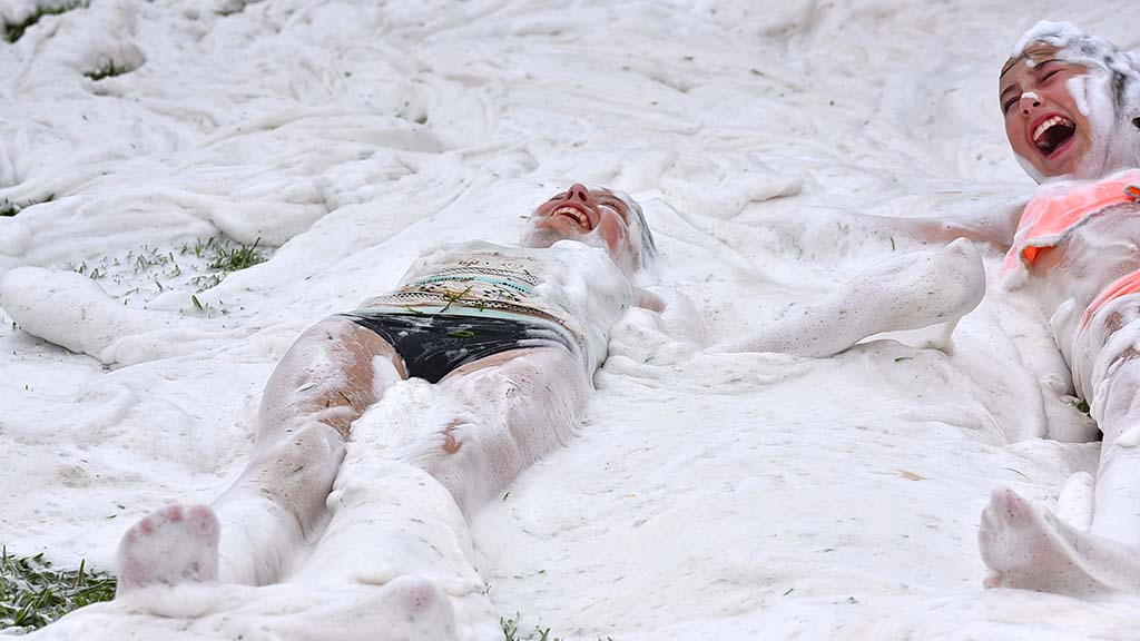 Two girls make snow angels in the blanket of foam at Crown Point on International Mud Day.