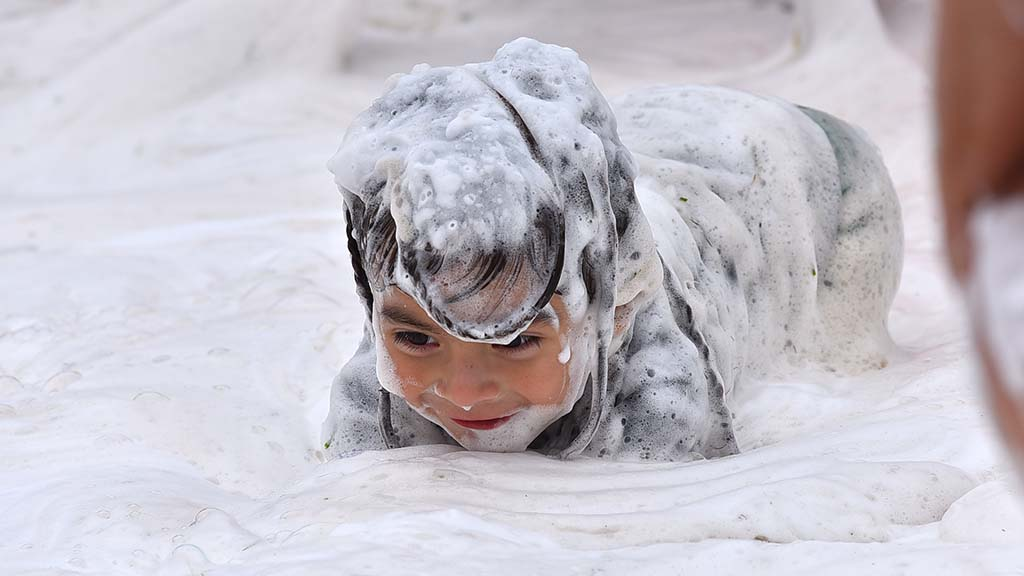A young child crawls through Dr. Bronner's Magic Soap at International Mud Day activities.