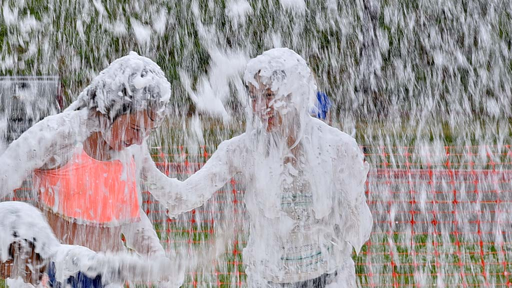 """Teens get cleaned off in a """"Snofoam Snowstorm"""" of soapy foam after participating in muddy fun."""