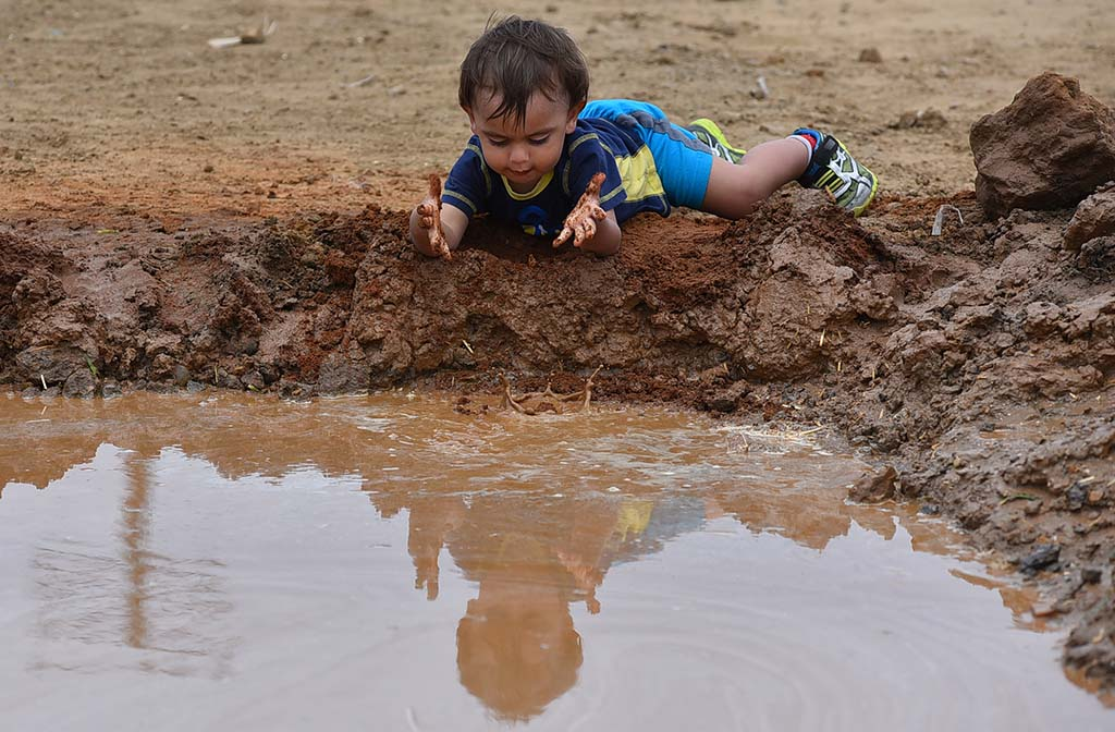 A toddler splashes mud into a water pit on the obstacle course at International Mud Day activities.