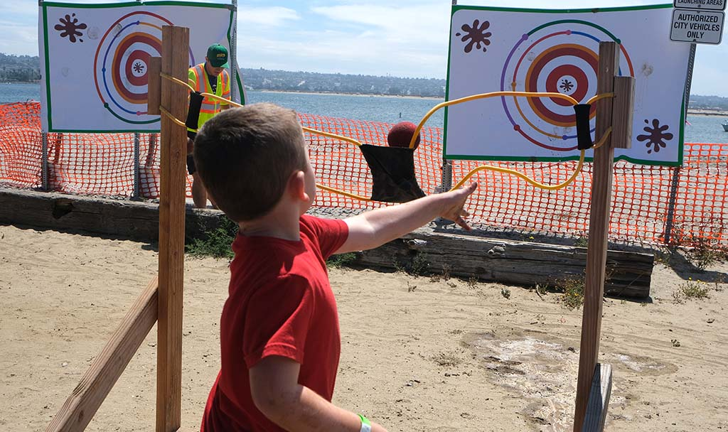 A boy lets go of a slingshot to propel a muddy ball toward a target at the Mud Day activities at Crown Point.