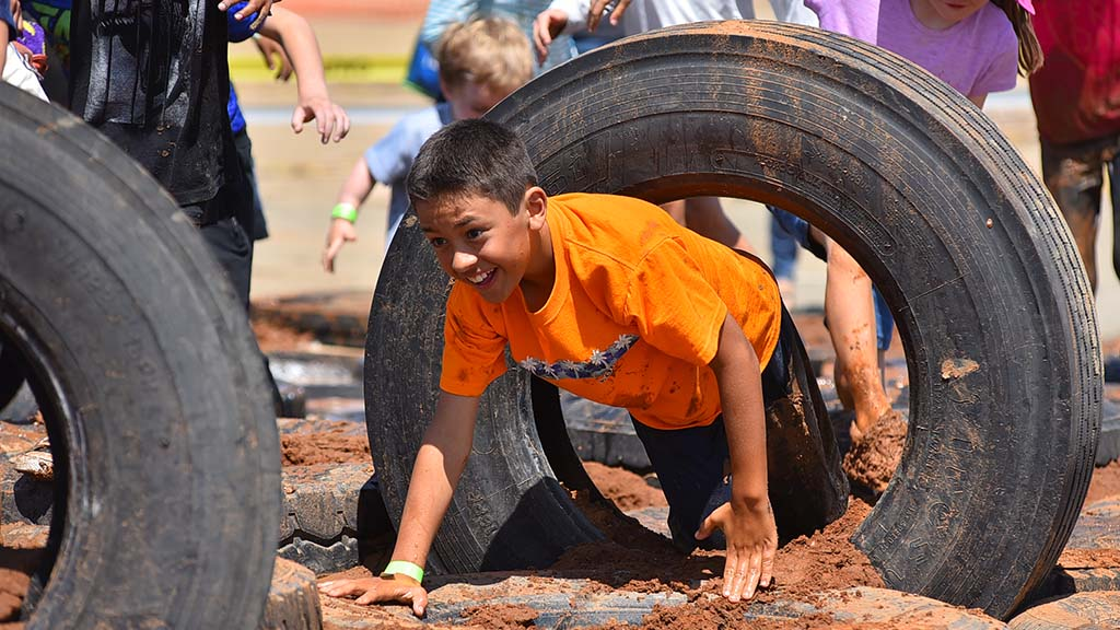 Participants crawled through tires during an obstacle course during San Diego's second annual celebration of International Mud Day.