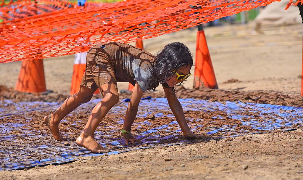 A girl scoots under plastic mesh during an obstacle course during Mud Day activities at Crown Point.