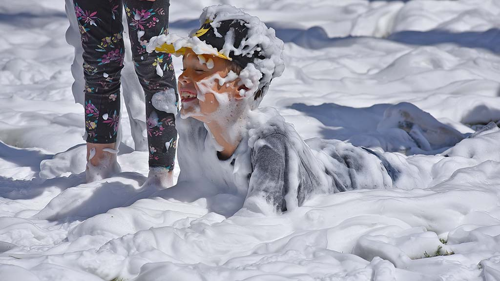 A boy settles into a bed of soapy foam at International Mud Day activities at Mission Bay.