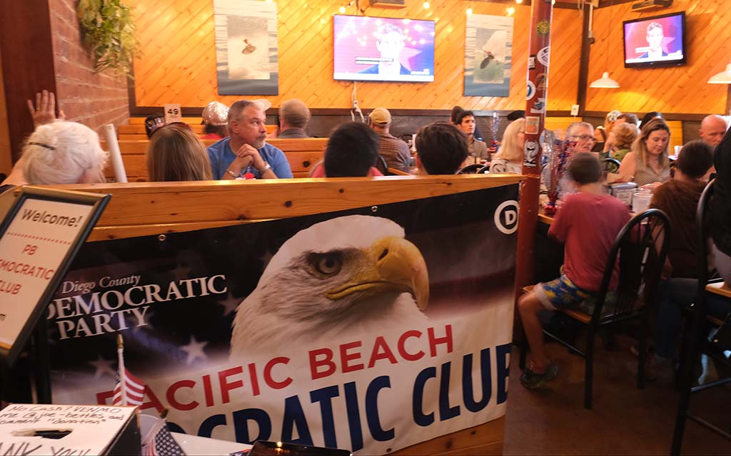 As Beto O'Rourke looks out from screens, an eagle stares from Pacific Beach Democratic Club banner at debate watch part