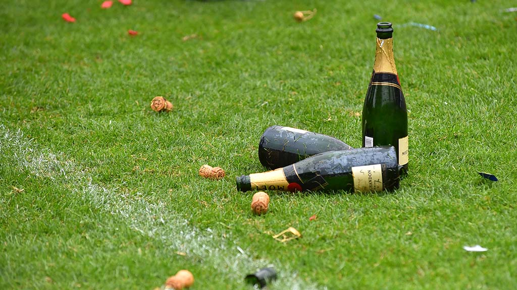 Champagne bottles, corks and confetti litter Torero Stadium field after Seattle victory in Major League Rugby title game.