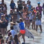 More than 100 fans of Bethany Hamilton surround the one-armed surfing star as she exits the water at the Nissan Surf Girl Surf Pro event.