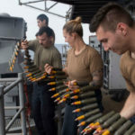 Sailors and Marines load ammunition on the USS Boxer