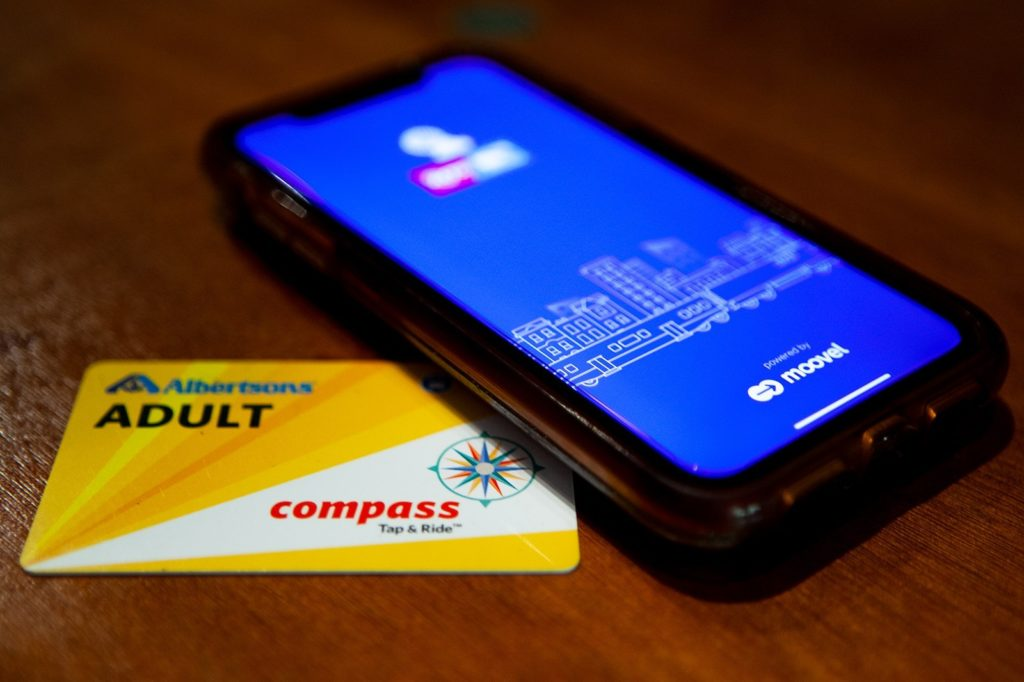 This photo, taken on July 9, 2019, shows MTS's adult Compass Card and the Compass Card app.