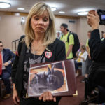 Animal rights advocate Deborah Classen holds a poster featuring rabbits
