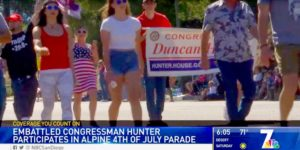 "Kris Wyrick (in ""Trump 2020"" shirt) and his wife, Rebecca (in flag colors dress) march with Rep. Duncan Hunter in Alpine parade. Image via NBC San Diego"