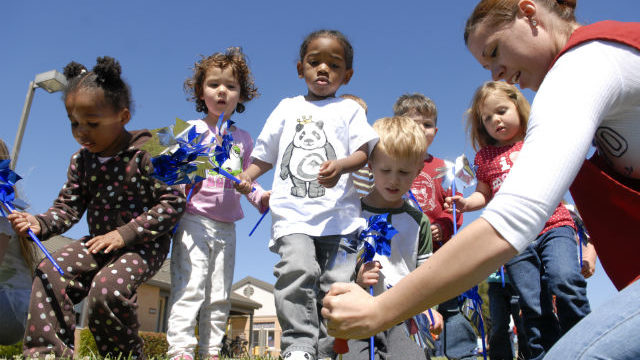 Children place pinwheels in recognition of Child Abuse Awareness Month