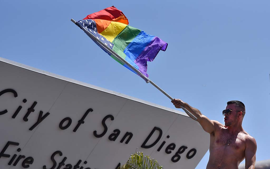 Joshua Kessler of Out of the Closet Thrift Stores waves a Pride American flag.