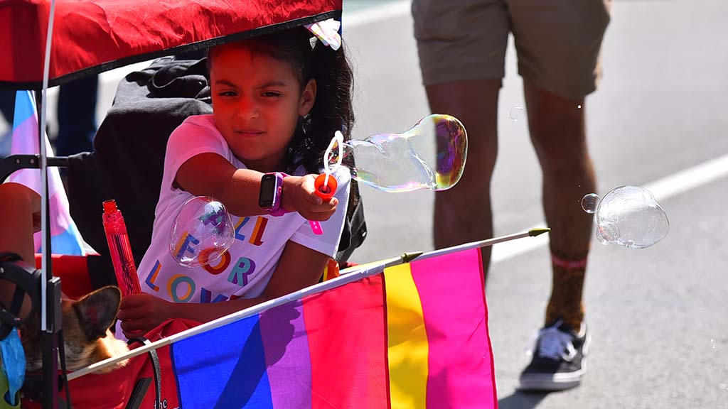 A girl creates bubbles for the spectators at the 2019 San Diego Pride Parade.