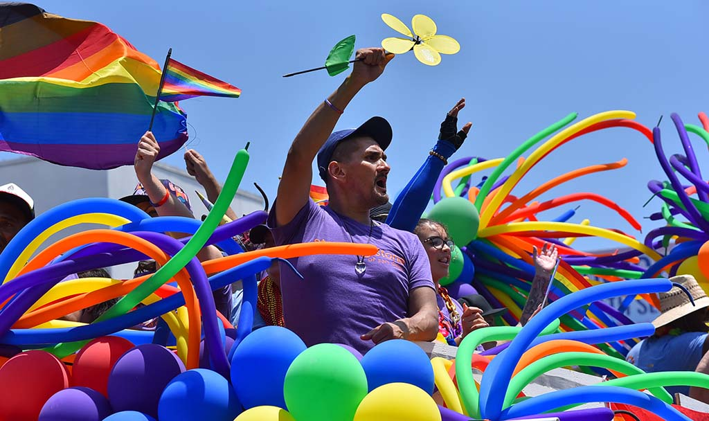 A member of Stepping Stone of San Diego sits amid a display of balloons.