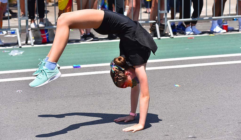 A girl with Creative Stages of San Diego flips as she makes her way down the parade route.