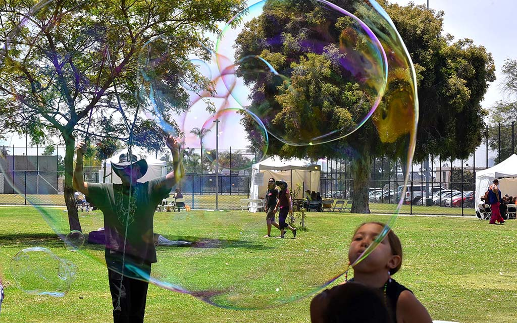 Alan James makes giant bubbles for children at the She Fest in North Park.